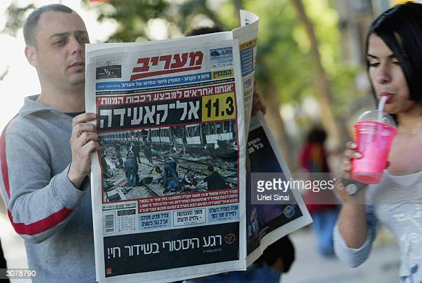 An Israeli man is reads a newspaper with images of yesterdays terror attacks in Madrid on the front page March 12 2004 in Tel Aviv Israel The Israeli...