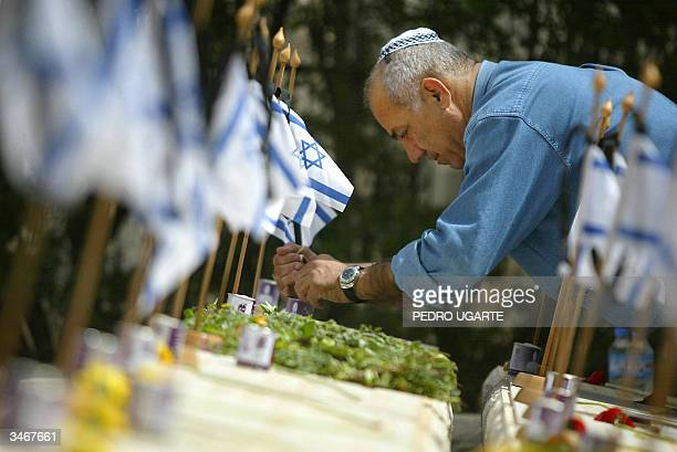 An Israeli man lights a candle at the grave of an Israeli killed during the 1948 war in the military cemetery on the Mount of Olives in Jerusalem...