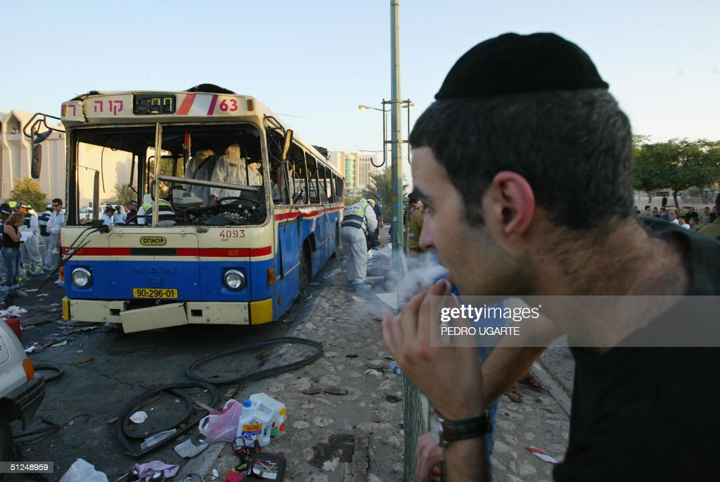 An Israeli man looks at a destroyed bus : News Photo