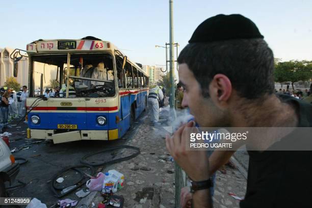 An Israeli man looks at a destroyed bus at the scene of a twin suicide bombing of two buses in the southern Israeli town of Beersheva 31 August 2004...