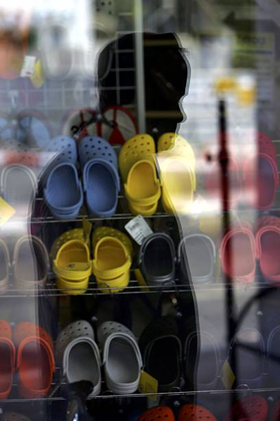 ca69f2a891cda An Israeli man pauses to look at a window display of Crocs shoes in a shoe