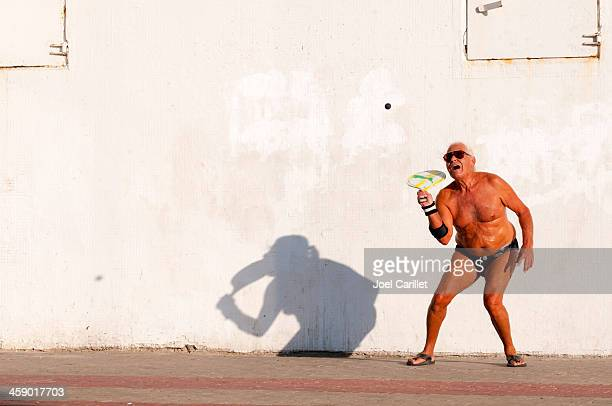 israeli man playing matkot in tel aviv - old man in speedo stock photos and pictures
