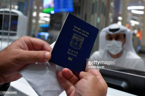 An Israeli man presents his passport for control upon arrival from Tel Aviv to the Dubai airport in the United Arab Emirates, on November 26 on the...