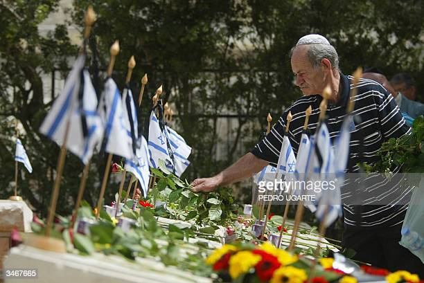 An Israeli man puts flowers on the grave of an Israeli killed during the 1948 war at the military cemetery on the Mount of Olives in Jerusalem during...