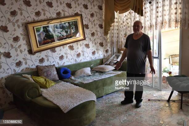 An Israeli man reacts as he inspects the damage caused to his appartment after being hit by sharpnel of a rocket fired from Gaza Strip in the...