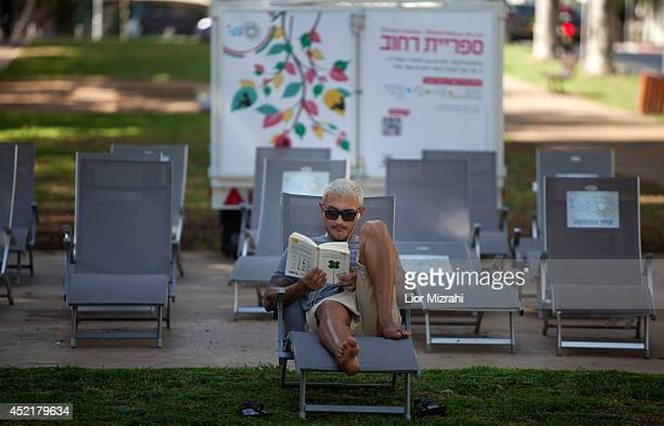 An Israeli man reads book on a bench on July 15 2014 in Tel Aviv Israel As operation 'Protective Edge' enters it's eighth day of airstrikes by the...