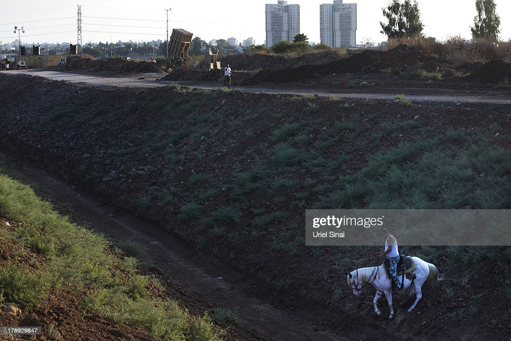 An Israeli man rides his horse past the 'Iron Dome' missile defense system as it is deployed on August 31, 2013 in Tel Aviv, Israel. Tensions are rising in Israel amid international talks of a military intervention In Syria. (Photo by Uriel Sinai/Getty Images)Ê