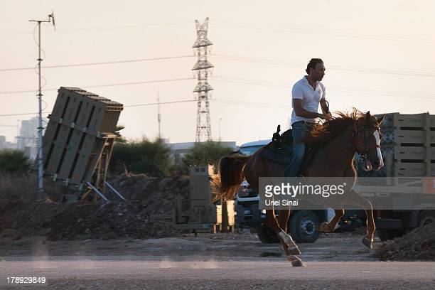 An Israeli man rides his horse past the 'Iron Dome' missile defense system as it is deployed on August 31, 2013 in Tel Aviv, Israel. Tensions are...