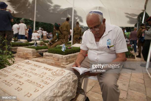 An Israeli man sits next to a grave at the military cemetery on April 18 2018 in Jerusalem Israel Israel marks the Remembrance Day to commemorate...