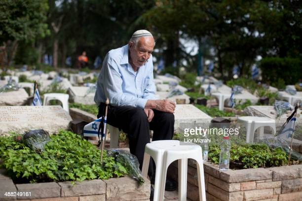 An Israeli man sits next to a grave of a fallen soldier at the military cemetery on May 5 2014 in Jerusalem Israel Israel marks the Remembrance Day...