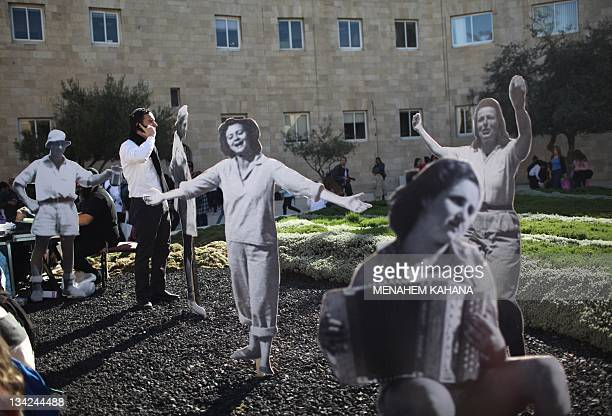 An Israeli man uses his mobile phone near lifesize cardboard cutouts during a ceremony reconstructing the celebrations that took place on November 29...