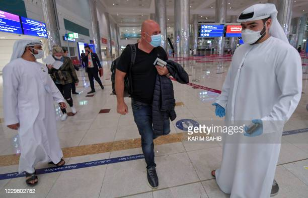 An Israeli man walks past Emirati staff after passport control upon arrival from Tel Aviv to the Dubai airport in the United Arab Emirates, on...
