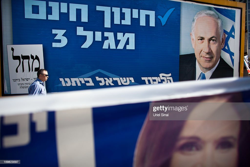 An Israeli man walks past posters of Israeli Prime Minister Benjamin Netanyahu and Israeli Labor party leader Shelly Yachimovich on January 21, 2013 in Tel Aviv, Israel. Israeli elections are scheduled for January 22 and so far showing a majority for the Israeli right.