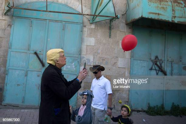An Israeli man wearing a mask of US President Donald Trump takes part in a parade celebrating the Jewish holiday of Purim on March 1 2018 in Hebron...