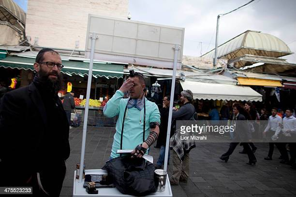 An Israeli man wears phylacteries and prays at Mahane Yehuda open market on February 27 2014 in Jerusalem Israel The Mahane Yehuda Market is over 100...