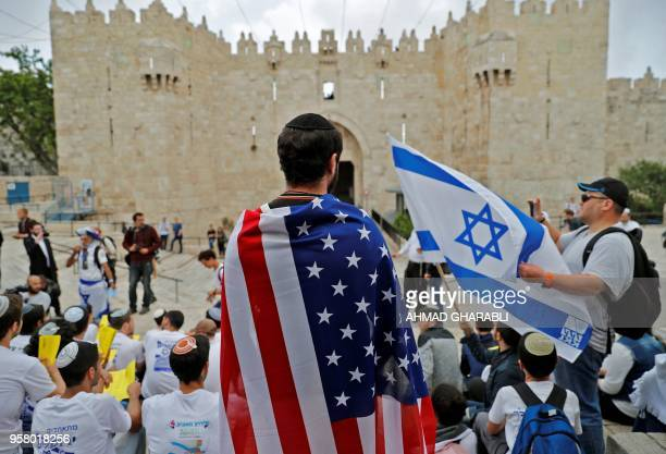 An Israeli man wears the US national flag at Damascus gate in Jerusalem on May 13 as Israeli nationalist settlers celebrate the Jerusalem Day in the...