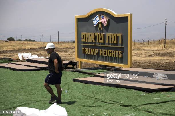 An Israeli man works near a sign for a new settlement named after US President Donald Trump on June 17, 2019 in Golan Heights, Israel. The Israeli...
