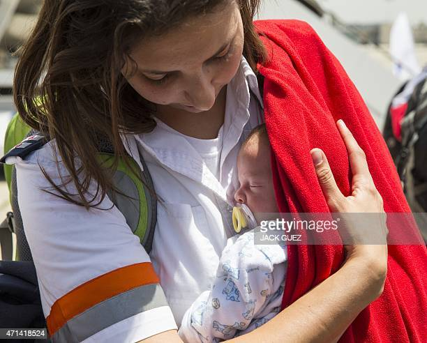 An Israeli medic carries the baby of a homosexual couple who had three infants born to surrogate mothers in Nepal after they arrived at Ben Gurion...