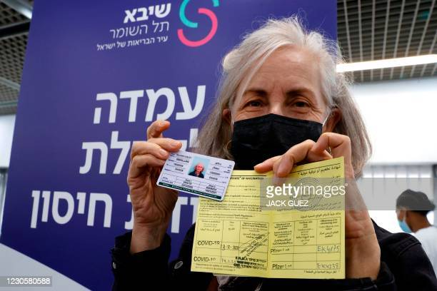 An Israeli medical worker presents her international card and certificate of vaccination after receiving a second Pfizer-BioNTech COVID-19 shot at...