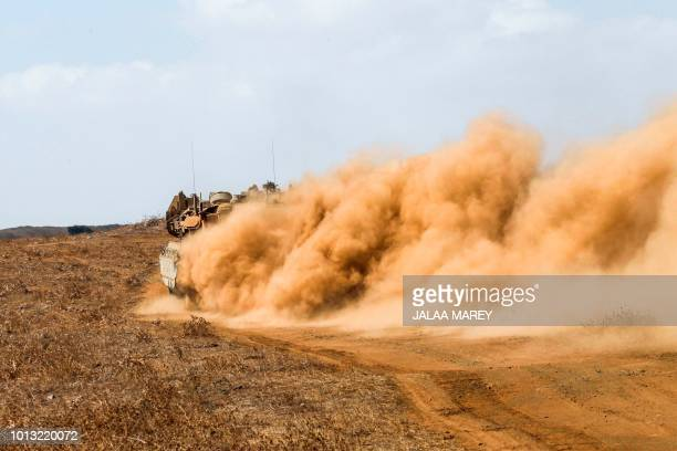 TOPSHOT An Israeli Merkava battle tank leaves a trail of dust as it speeds during a military exercise in the Israeliannexed Golan Heights along the...