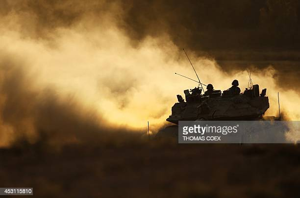 An Israeli Merkava tank drives back from the Gaza Strip to an Israeli base at the IsraeliGaza border during the sunset on August 3 2014 A Palestinian...