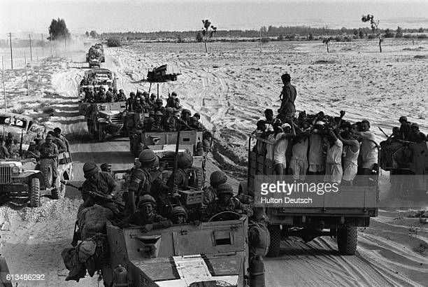 An Israeli military convoy passes a truck carrying Egyptian prisoners travelling in the opposite direction during the SixDay War