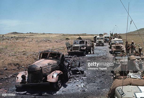An Israeli military convoy passes destroyed vehicles during the SixDay War By June 10 when the fighting was halted Israel had won territory four...