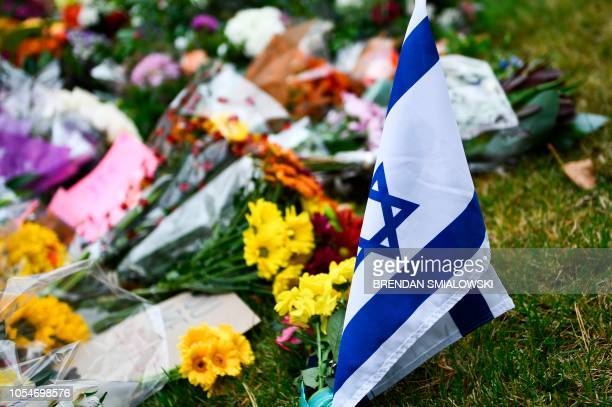 An Israeli national flag is seen at a memorial on October 28 down the road from the Tree of Life synagogue after a shooting there left 11 people dead...