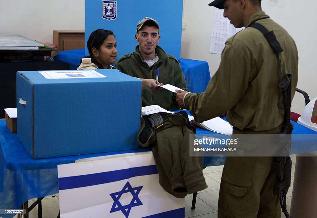 An Israeli Navy soldier presents his documents prior to vote at an army Navy base in Ashdod, on January 20, 2013. Israeli soldiers started to vote for the 19th Israeli general election. Thirty-eight parties are running on 34 lists in Israel's general election to be held on January 22.