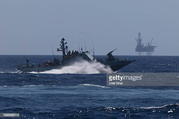An Israeli Navy vessel passes by the Tamar drilling natural gas production platform during a squadron exercise on May 27 2013 off the coast of Israel...
