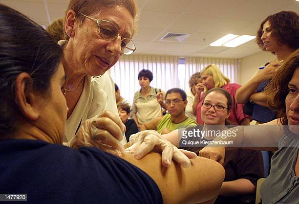An Israeli nurse inoculates a woman with Vaccinia an antidote for smallpox on September 2 2002 at the Tel Hashomer hospital in Tel Aviv Israeli...