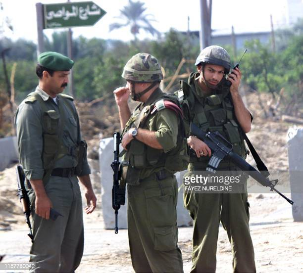 An Israeli officer confers with a Palestinian officer to arrange the removal of concrete blocks from the road at Gush Katif crossing 30 October 2000...