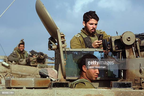 An Israeli officer makes a call on his mobile phone on leaving the Gaza Strip after supporting troops fighting Palestinian militants March 2 2008...