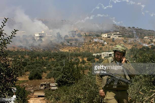 An Israeli officer speaks on his radio as soldiers try to recover a disabled Israeli tank after it was hit by a Hezbollah rocket while in the...