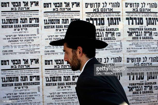 An Israeli Orthodox Jew walks past death notices mourning the killing of four Jews in southern France this week in Jerusalem on March 22 2012...