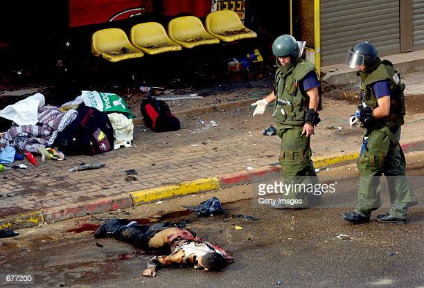 An Israeli police bomb disposal unit investigates the site of a suicide bombing December 9 2001 in the northern Israeli city of Haifa where the body...