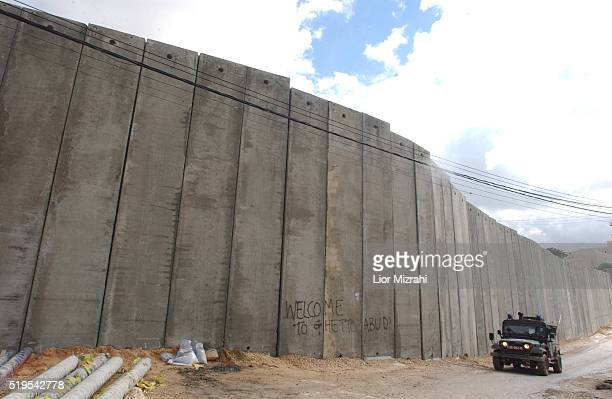 An Israeli police jeep passes next to the concrete wall separating east Jerusalem from the West Bank village of Abu Dis Sunday Feb 01 2003