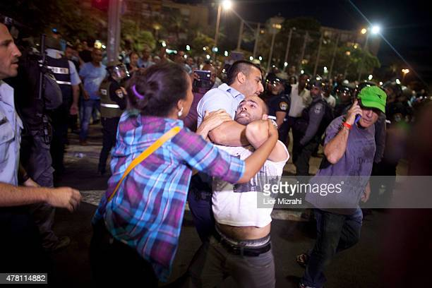 An Israeli Police officer arrests a man as Israelis of Ethiopian origin protest against racism and excessive aggression by Israeli police on June 22...