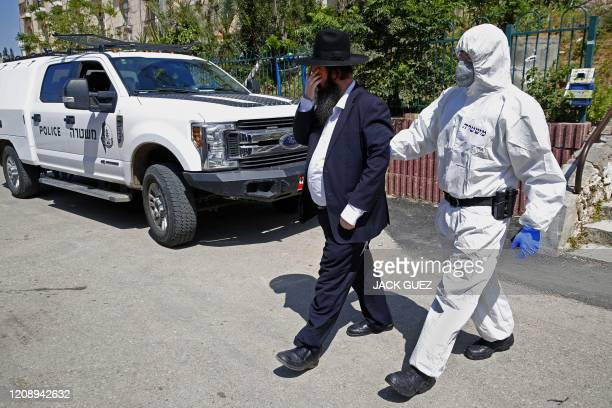 An Israeli police officer dressed in protective outfit leaves a Yeshiva with an arrested Orthodox Jew in the Israeli city of Bnei Brak on April 2...