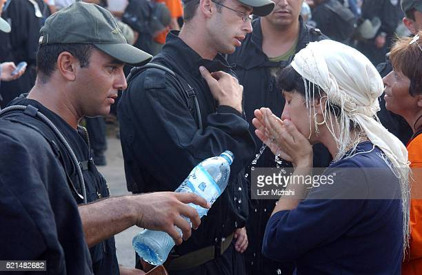 An Israeli police officer giving a settler woman water in front of a police line just inside the main gates of Neveh Dekalim Gush Katif Gaza Strip on...