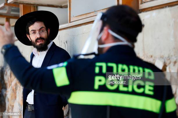 An Israeli police officer speaks to an ultraOrthodox Jewish student at a Yeshiva in Bnei Barak a city east of Tel Aviv with a significant...