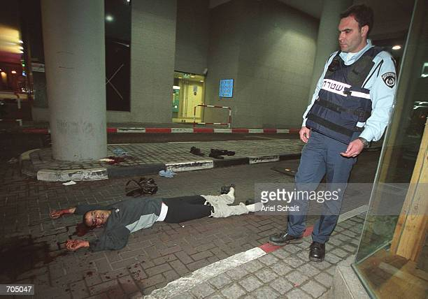 An Israeli police officer stands next to the body of a victim killed by a Palestinian gunman in front of a restaurant March 5, 2002 in Tel Aviv. The...