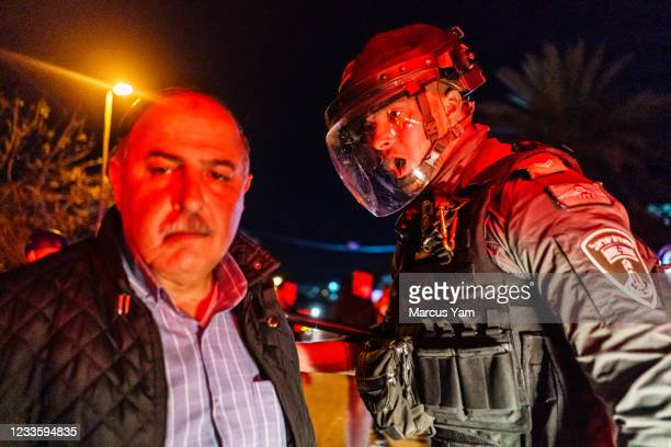 An Israeli police officers yells at a Palestinian man to disperse from the streets as unrest ensues in the Sheikh Jarrah neighborhood of East...