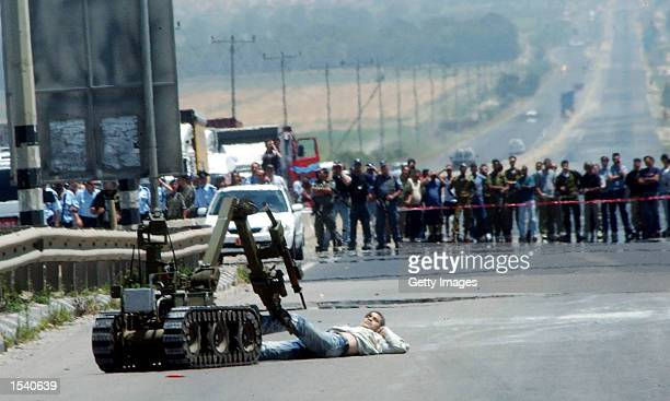 An Israeli police robot drags a critically wounded Palestinian bomber May 8 2002 at Megido Junction south of Haifa Israel The bomber detonated...