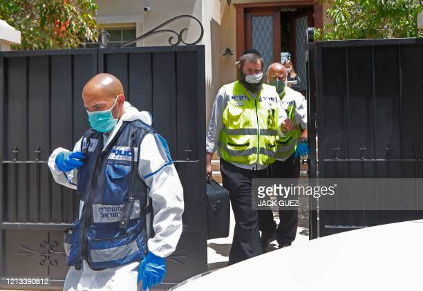 An Israeli policeman and forensic experts walk out of Israel's Chinese ambassador's residence on the outskirts of Tel Aviv, after he was found dead...