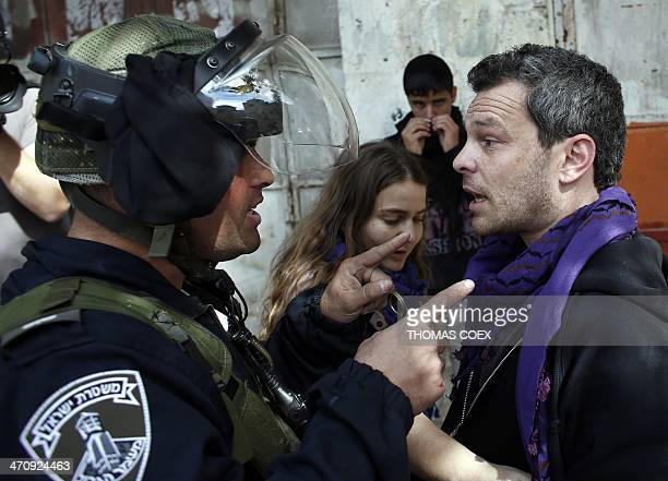 An Israeli policeman argues with an Israeli peace activist in the centre of the West Bank city of Hebron on February 21 2014 during a demonstration...