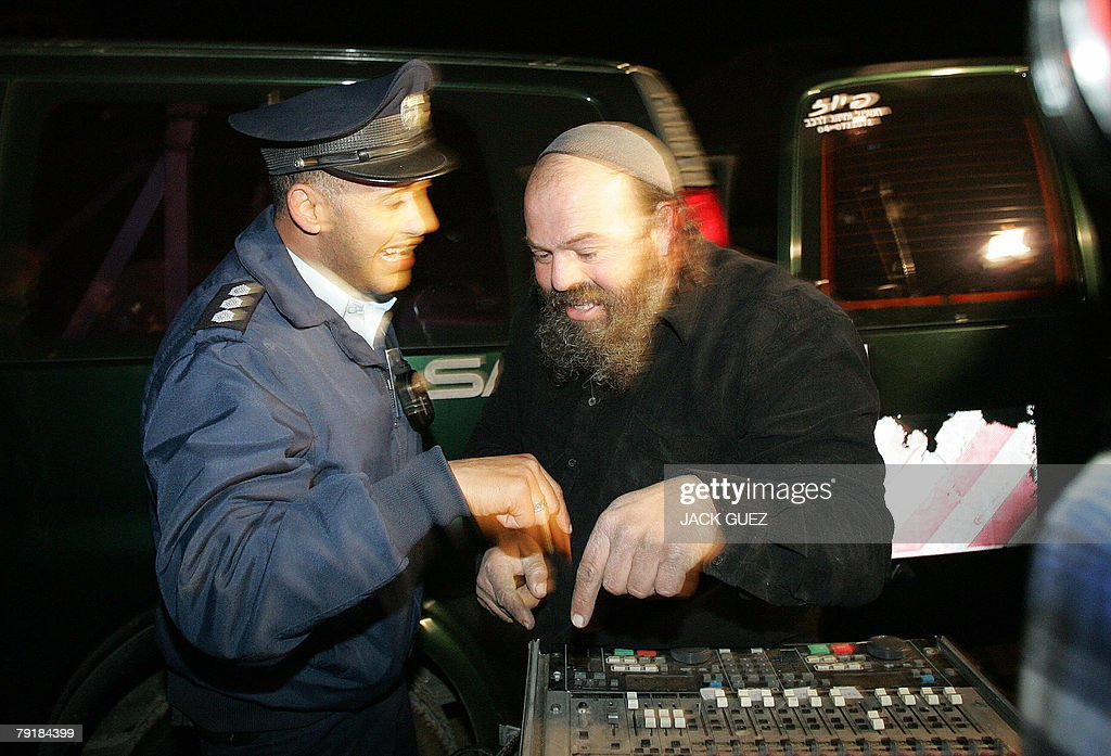 An Israeli policeman asks an ultra-Orthodox Jewish man to switch off loud music during an Israeli army reservists demonstration against Israeli Prime Minister Ehud Olmert's politics as he gives a speech at a security conference in the coastal town of Herzliya, near Tel Aviv, late 23 January 2008. Olmert said today he was determined to strike a peace accord with the Palestinians, saying the current leadership was the best to negotiate with.
