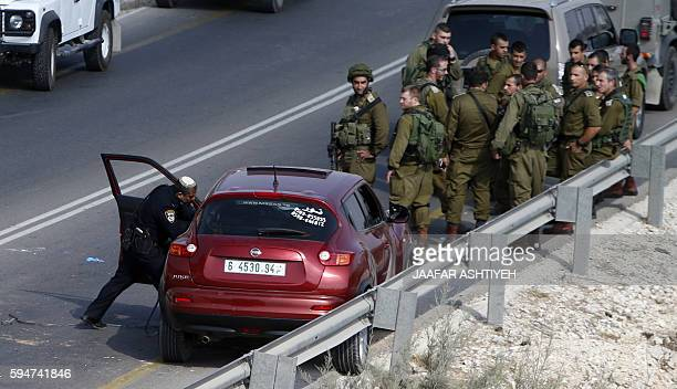 An Israeli policeman checks a car from which a Palestinian reportedly exited and stabbed an Israeli soldier before being shot dead on August 24 2016...