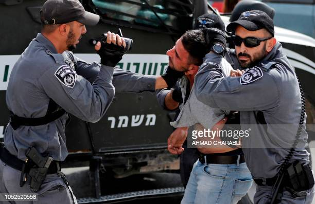 TOPSHOT An Israeli policeman films a Palestinian as others hold him as he is being detained during a demonstration at the Palestinian Bedouin village...