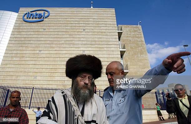 An Israeli policeman gestures as he escorts an UltraOrthodox Jewish protester during a demonstration outside Intel company in Jerusalem's Hozvim...